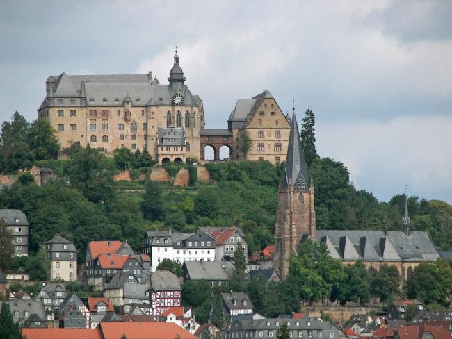 Das Bild zeigt die malerische Kulisse der Lutherischen Pfarrkirche in Marburg. Das beeindruckende Gebäude biete die Bühne für die ganz besonderen Konzerte am 26.9.21. Dabei sorgt das 50jährige Jubiläum der Schlosskonzerte für Auftritte von bekannten Künstlern und Künstlerinnen. (c) Wikimedia Commons.