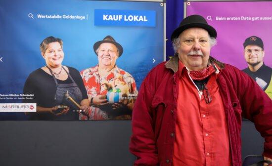 """""""Mit uns können die Leute reden, sich austauschen"""", nennt Fiddy Bode von Comics, Kitsch&Kunst den großen Vorteil des lokalen Handels, der """"Gesicht"""" zeigt. Bode ist einer von 16 Einzelhändler*innen, die auf den Plakaten der Kampagne »Kauf lokal« stellvertretend für die ganze Branche zu sehen sind. (Foto: Patricia Grähling, Stadt Marburg)"""